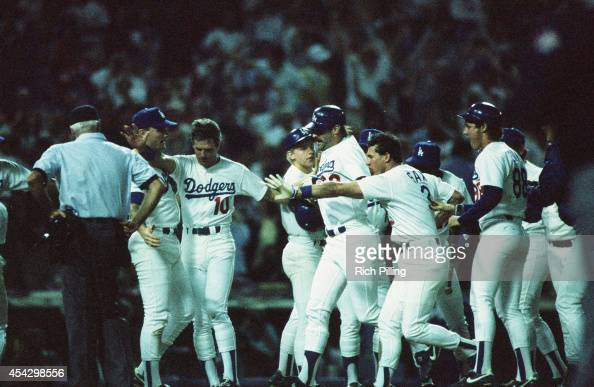 Kirk Gibson of the Los Angeles Dodgers is mobbed by his teammates after hitting the game winning home run in the bottom of the ninth inning during...