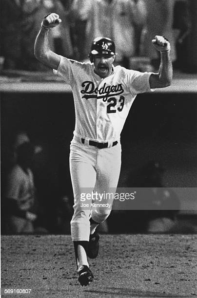 Kirk Gibson of the Los Angeles Dodgers raises his arms in celebration as he rounds the bases after hitting the game– winning two run homer in the...