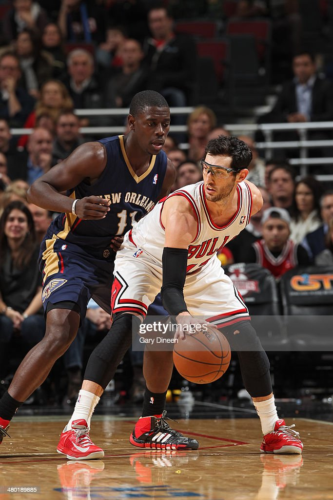 Kirk Hinrich #12 of the Chicago Bulls handles the ball against Jrue Holiday #11 of the New Orleans Pelicans on December 2, 2013 at the United Center in Chicago, Illinois.