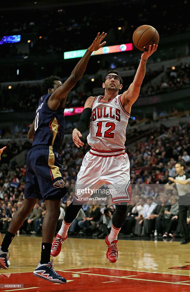 Kirk Hinrich #12 of the Chicago Bulls puts up a shot around Al-Farouq Aminu #0 of the New Orleans Pelicans at the United Center on December 2, 2013 in Chicago, Illinois. The Pelicans defeated the Bulls 131-128 in triple overtime.