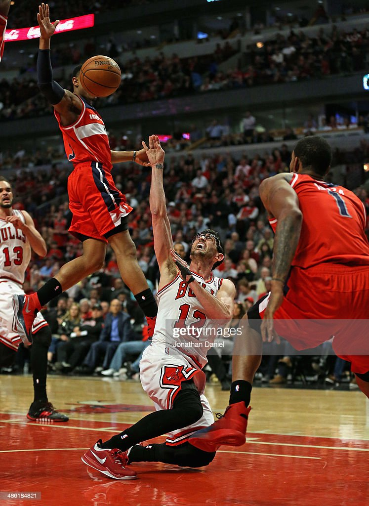 <a gi-track='captionPersonalityLinkClicked' href=/galleries/search?phrase=Kirk+Hinrich&family=editorial&specificpeople=201629 ng-click='$event.stopPropagation()'>Kirk Hinrich</a> #12 of the Chicago Bulls tries to get off a shot as he hits the floor between <a gi-track='captionPersonalityLinkClicked' href=/galleries/search?phrase=Bradley+Beal&family=editorial&specificpeople=7640439 ng-click='$event.stopPropagation()'>Bradley Beal</a> #3 (L) and <a gi-track='captionPersonalityLinkClicked' href=/galleries/search?phrase=Trevor+Ariza&family=editorial&specificpeople=201708 ng-click='$event.stopPropagation()'>Trevor Ariza</a> #1 of the Washington Wizards in Game Two of the Eastern Conference Quarterfinals during the 2014 NBA Playoffs at the United Center on April 22, 2014 in Chicago, Illinois. The Wizards defeated the Bulls 101-99.