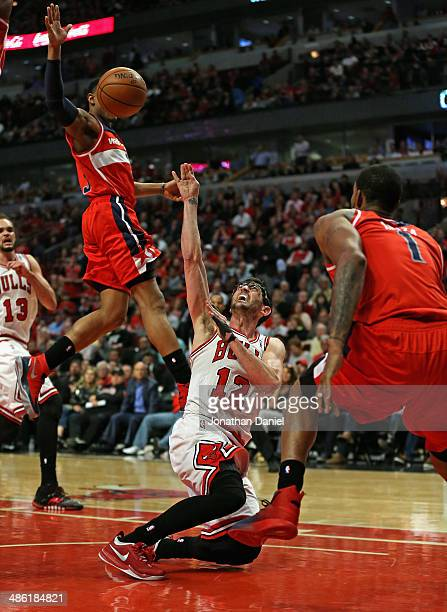 Kirk Hinrich of the Chicago Bulls tries to get off a shot as he hits the floor between Bradley Beal and Trevor Ariza of the Washington Wizards in...