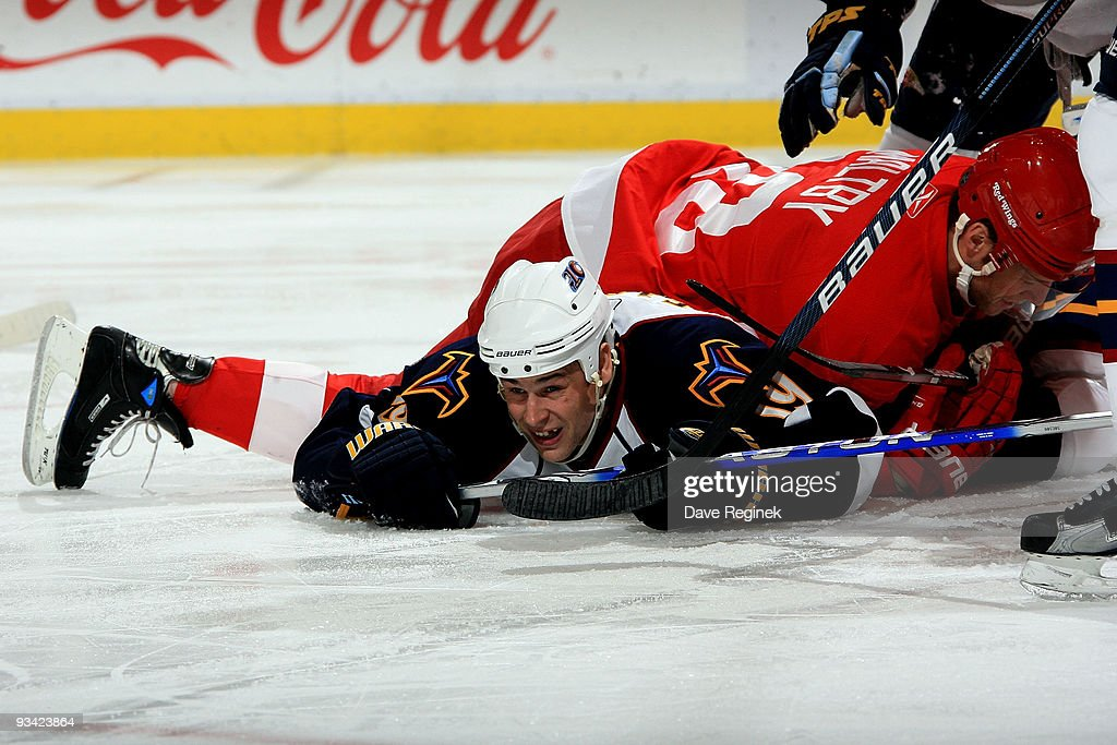 Kirk Maltby #18 of the Detroit Red Wings gets tangled up with Marty Reasoner #19 of the Atlanta Thrashers during a NHL game at Joe Louis Arena on November 25, 2009 in Detroit, Michigan.