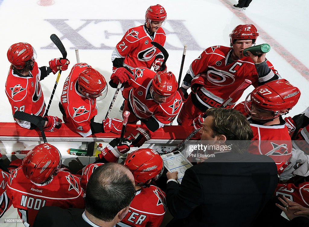 Kirk Muller, coach of the Carolina Hurricanes, discusses strategy with his team during a timeout in an NHL game against the New York Rangers on March 1, 2012 at RBC Center in Raleigh, North Carolina.