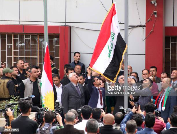 Kirkuk provincial Governor Najim alDin Karim raises the Iraqi flag to fly next to the Kurdish flag over a government building in the northern Iraqi...