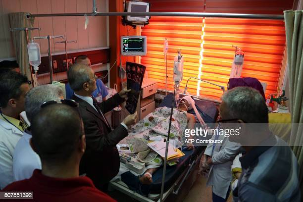 Kirkuk provincial Governor Najm alDin Karim reads an xray during a visit to wounded pashmerga soldiers at a hospital in Kirkuk on July 4 2017 / AFP...