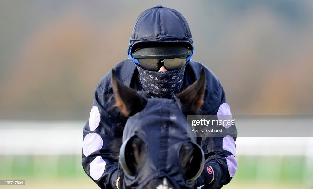 Kirsty Milczarek protects her face from the cold at Lingfield racecourse on December 06, 2012 in Lingfield, England.