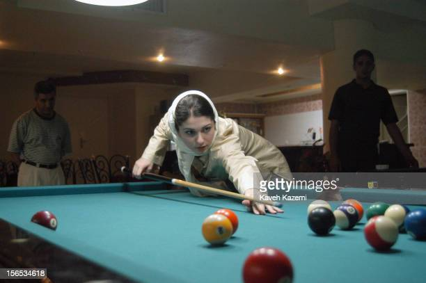A young veiled Iranian woman plays a game of pool in a club in Kish Iran Pool game was forbidden until two years ago Due to lesser restrictions on...