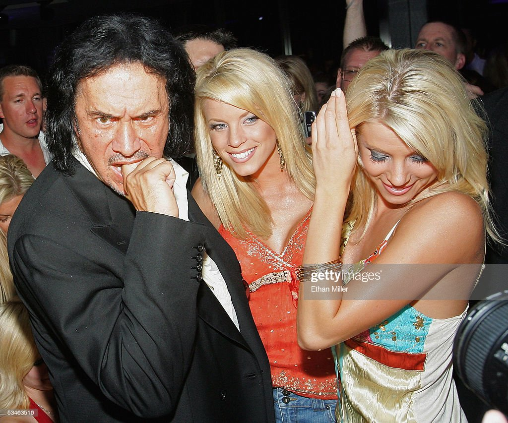 Kiss singer/bassist Gene Simmons poses with 'Palms Girls' models, twin sisters Ruth Quinn (C) and Ryan Wahrenbrock (R) during his birthday party at the Palms Casino Resort August 25, 2005 in Las Vegas, Nevada.