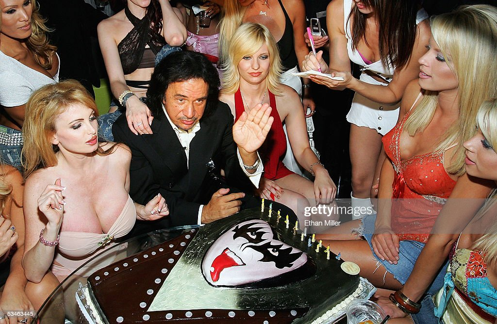 Kiss singer/bassist Gene Simmons waves during his birthday party at the Palms Casino Resort August 25, 2005 in Las Vegas, Nevada. Adult film actress Taylor Wane looks on at left.