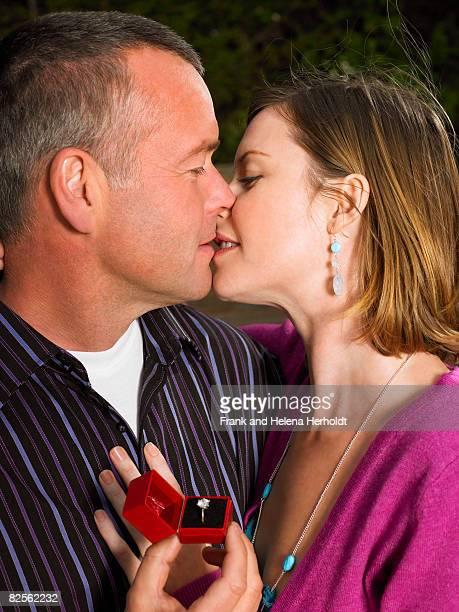 Kissing couple, holding engagement ring