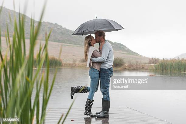 Kissing couple standing in the rain with umbrella