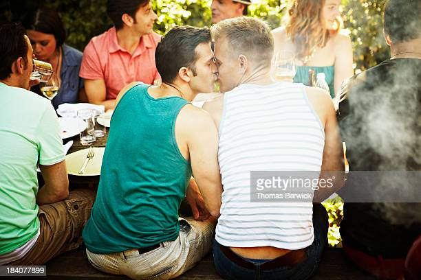 Kissing gay couple sitting at table with friends