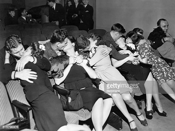 Soldiers and sailors reunited with theirwives in a theater during World War II
