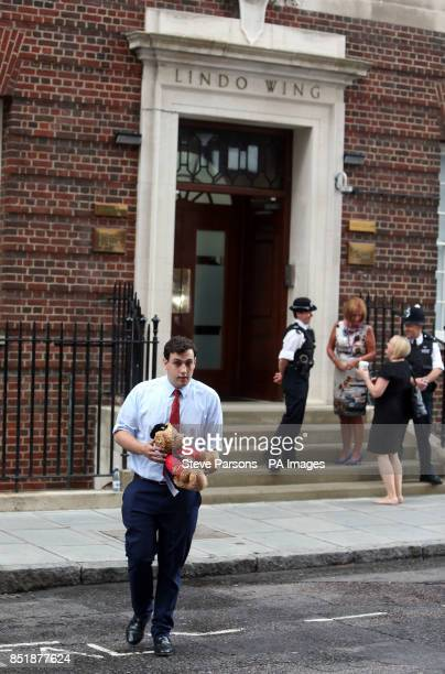 Kit Arkwright from British Horse Racing delivers a teddy bear dressed in the Queen's racing colours outside St Mary's Hospital in London as the world...