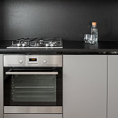 Gray kitchen cabinet, black backsplash, oven and hob