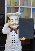 cute figurine or a kitchen chief with a blackboard standing in front of a restaurant