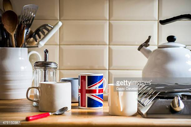 Kitchen counter with jug of utensils and coffee mugs