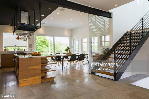 Kitchen, dining room and American walnut wood and black powder coated cold rolled steel stairs inside a modern cube style home, Quebec, Canada