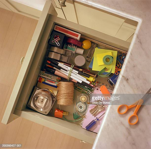 Kitchen drawer containing household items, overhead view