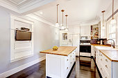 Kitchen interior in white tones with hardwood counter tops, kitchen island and black tile back splash trim. White coffered ceiling with pendant lights make room more elegant.