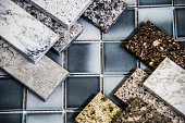 Kitchen natural stone counter tops color samples over floor tiles samples