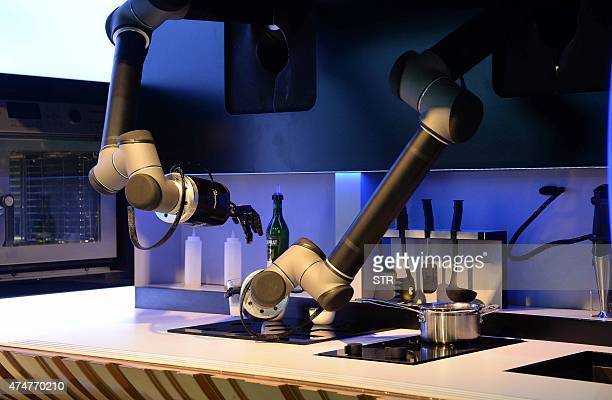 A kitchen robot from Mloey Robotics cooks food for visitors during the first Consumer Electronics Show in Asia in Shanghai on May 26 2015 More than...