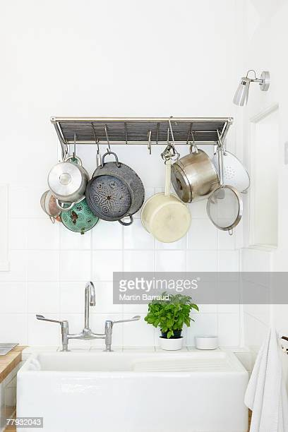 Kitchen sink with cooking pots hanging overhead