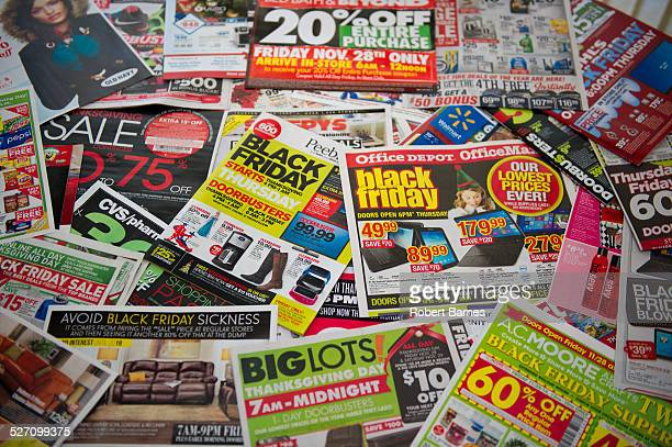 A kitchen table full of 'Black Friday' Sale Circulars with Sale Promotions from various Retailers