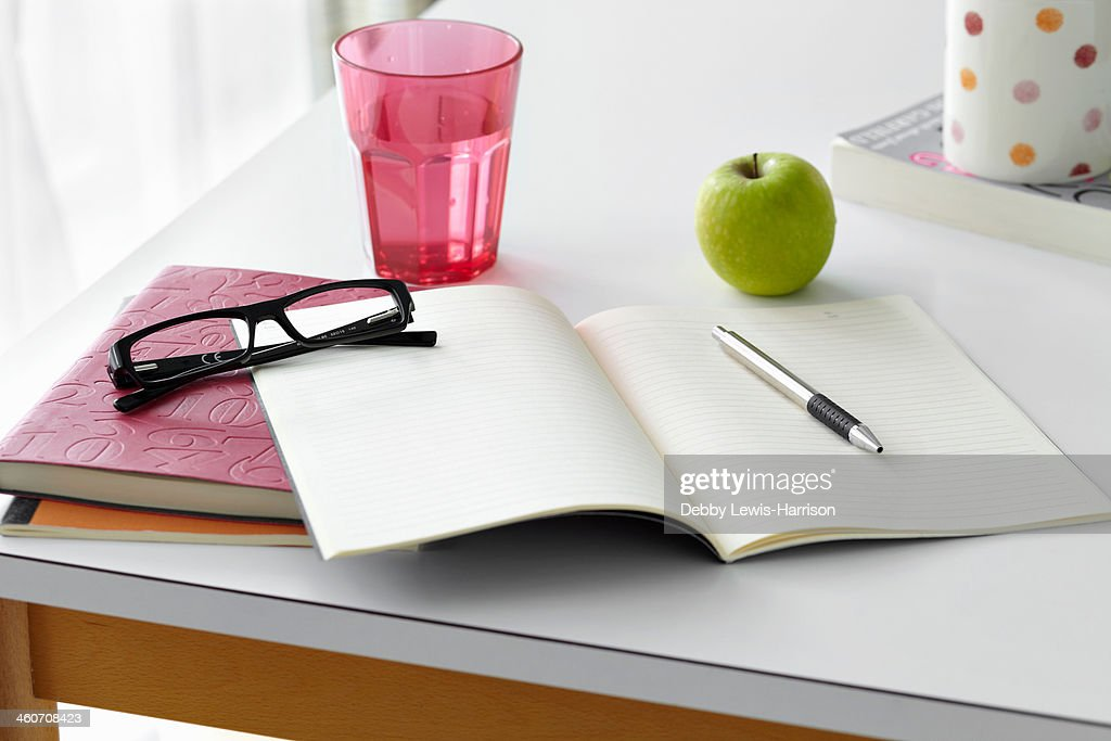 Kitchen table still life with notebooks, spectacles and apple