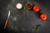 Dark gray stone (concrete) kitchen table with a knife, spices, herbs and vegetables. cooking background. Top view, copy space