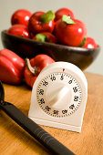 Kitchen timer on counter with bowl of apples and peppers