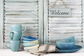 Simple rustic handmade blue crockery against shabby wooden shutters: dish, bowls, mugs and Welcome plate.