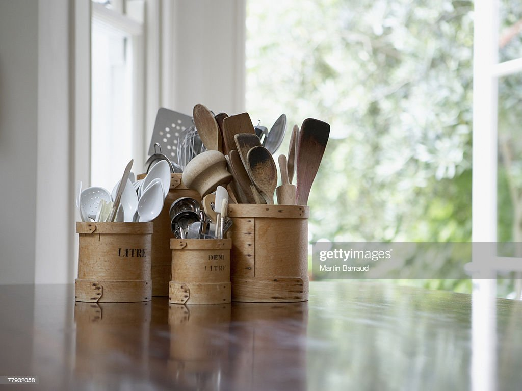 Kitchen utensils in containers on table