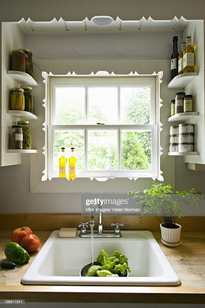 Kitchen window, with shelves and a traditional sink, tap and running water for washing vegetables. : Stock Photo