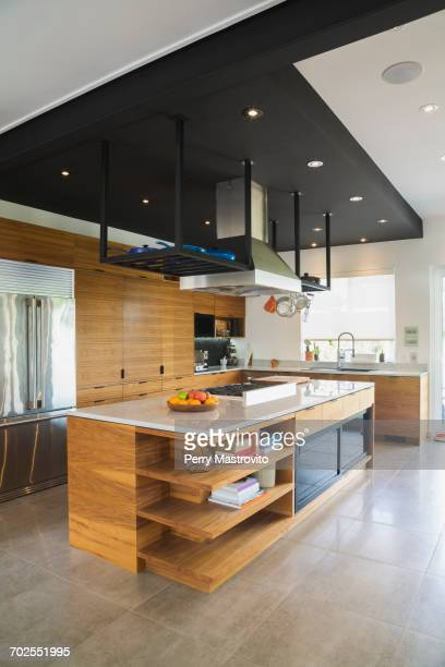 Kitchen with American walnut wood island, cabinets and quartzite countertops inside a modern cube style home, Quebec, Canada