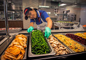 A kitchen worker sets up the salad bar at the FDA cafeteria for our story on federal agencies bedeviled by shortage of chefs and cooks with security...