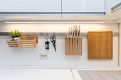 kitchenware hanging on the rail in the white glossy kitchen