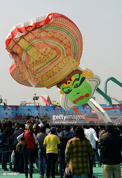 A kite designed as a 'Kathakali Dancer' a traditional dance form of Kerala lifts off during the International Kite Festival in Ahmedabad on January...