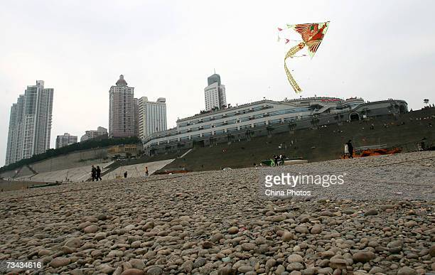 A kite flies above the dry riverbed of the low Yangtze River which has dropped around 40 percent at the Chaotianmen dock on February 27 2007 in...
