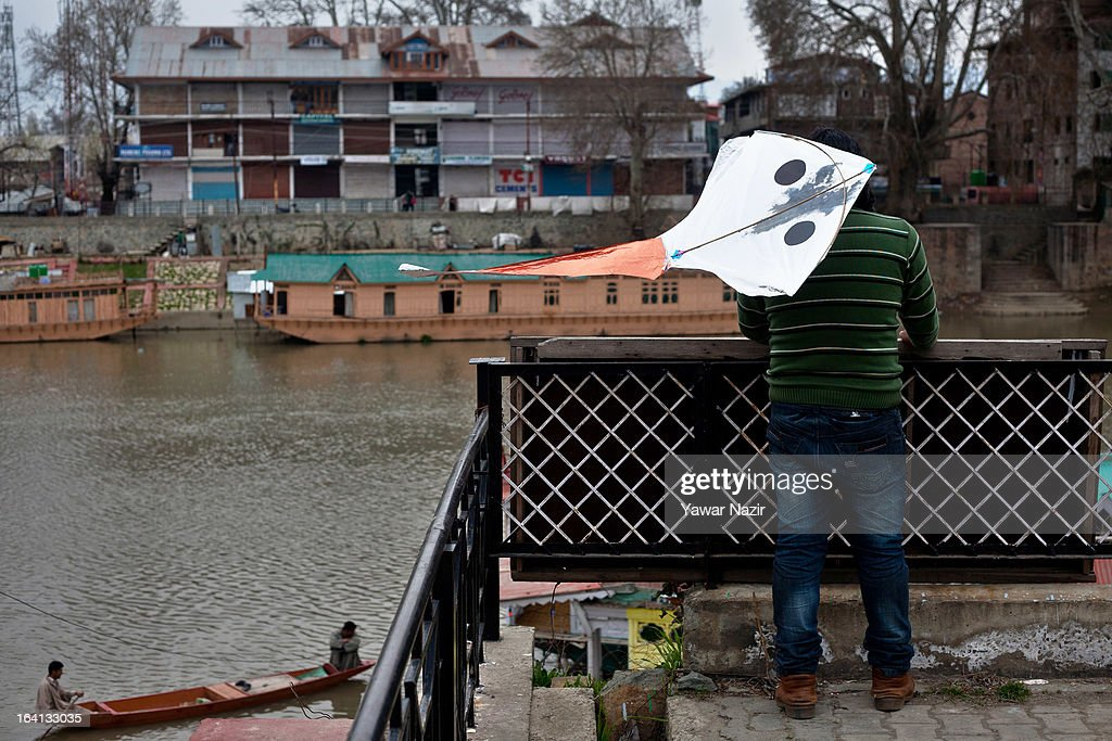 A kite flies from a man's back as he looks at a view of the river Jehlum on March 20, 2013 in Srinagar the summer capital of Indian administered Kashmir, India. Kashmir has been a contested land between nuclear neighbors India and Pakistan since 1947, the year both the countries attained freedom from the British. Since 1947 the ownership of Kashmir has been disputed between Pakistan, India and China.
