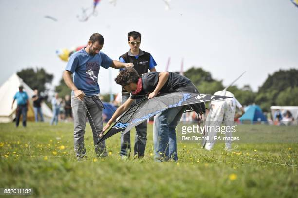 Kite flyers untangle lines on an insect kite shaped like a butterfly at the Bristol International Kite Festival held on the Ashton Court Estate which...