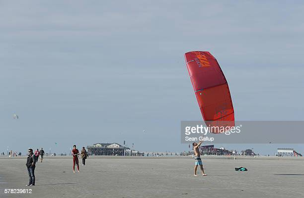 A kite surfer gets help hauling in his kite at a beach on July 18 2016 at SanktPeterOrding Germany SanktPeterOrding is among the top destinations for...