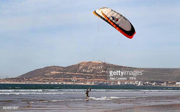 A kite surfer surfs along the Bay of Agadir as a memorial is seen in the background in the old town area below the walls of the original Kasbah on...