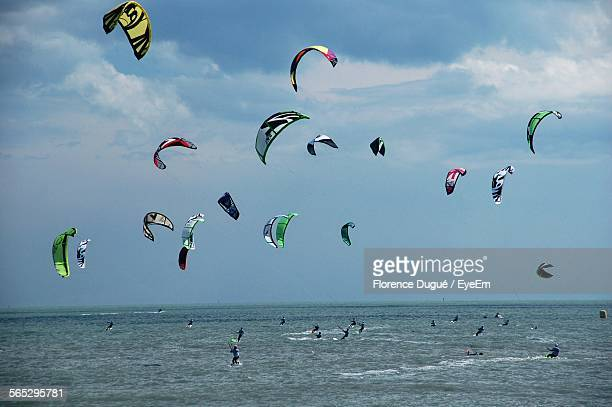 Kite Surfers At Beach Against Cloudy Sky