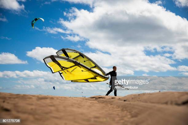 TOPSHOT A kitesurfer carries his kite on a sandbank at low tide in the estuary of the river Exe as it runs into the English channel by Exmouth in...