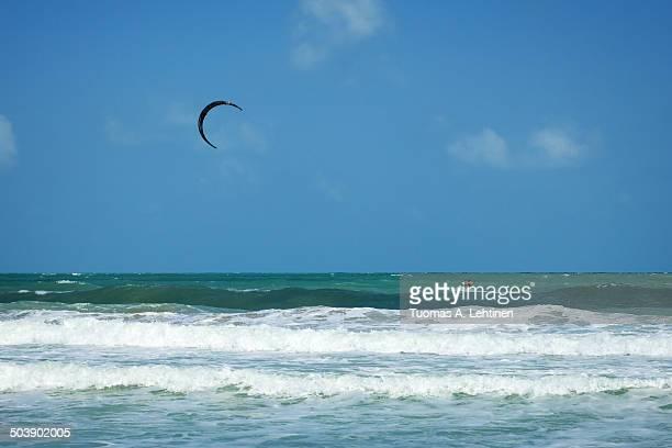A kitesurfer kiteboarding at ocean in Koh Samui