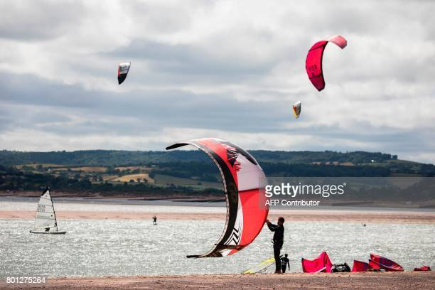 A kitesurfer prepares his kit in the estuary of the river Exe as it runs into the English channel by Exmouth in south west England on June 25 2017 /...