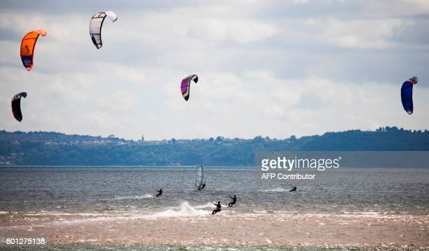 TOPSHOT Kitesurfers catch the wind in the estuary of the river Exe as it runs into the English channel by Exmouth in south west England on June 25...