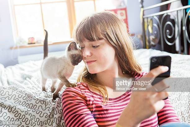 Kitten gives cuddles to teenager with phone.